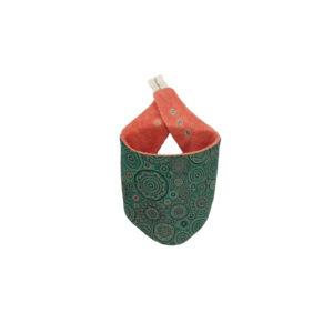 Wonderlands_baby gift_handmade bandana bib_Black & light orange rounds of different sizes on a green background_shweshwe_cotton towel of coral colour_closed