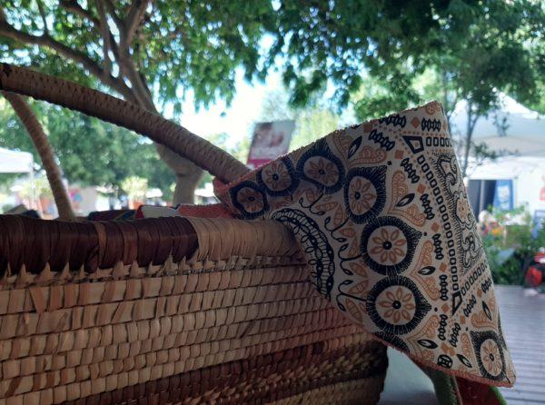 bandana bib_Frida K fabric_cotton towel of coral colour_on a woven basket