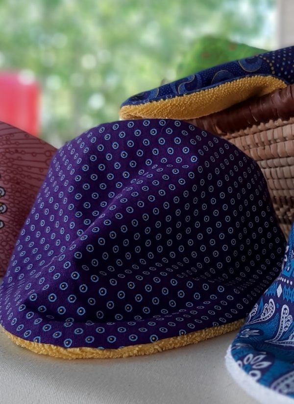 Wonderlands_baby gift_handmade bandana bib_White dots on a dark purple background - Three Cats shweshwe_cotton towel of golden colour_close up