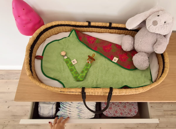 pacifier clip_Coco C fabric on a fynbos baby changing mat in a handmade moses basket with a hand
