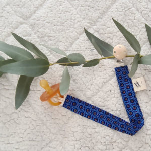 pacifier clip_Michelle O fabric on a bed with with dummy and foliage