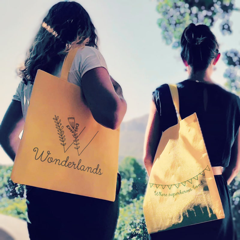 Fleur & Cecile from the back looking at the capetonian mountains_wearing yellow bags with Wonderlands logo