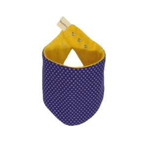 Wonderlands_baby gift_handmade bandana bib_White dots on a dark purple background - Three Cats shweshwe_cotton towel of golden colour_closed