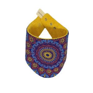 Wonderlands_baby gift_ handmade bandana bib_Red, yellow & light blue rosette on a dark blue background_Three Cats shweshwe_cotton towel of golden colour_closed